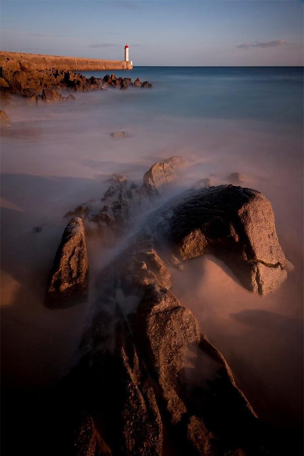 De foto is gemaakt op 29 april 2013 voor de kust van Bretagne, bij het dorpje Audierne. De kade met de vuurtoren wijzen in zuidelijke richting zodat de ondergaande zon een prachtige warme avondsfeer achterlaat. Ik vond dat de rustige sfeer van het avondlicht ook een rustige sfeer van de zee nodig had en ik koos voor een 10stops grijsfilter om de sluitertijd te verlengen. De originele sluitertijd ging daardoor van 1/10 seconden naar bijna 100 seconden waardoor het stromende water een zijdezachte waas werd. Avondlicht: ISO 220, F 22, 98 seconden / Ben Töller